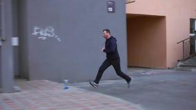 Köra för ung man som är utomhus-, till och med kvarter på en gata stock video