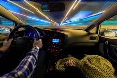 Köra i nattlandskap, händer på styrninghjulet, nattregntid arkivbild
