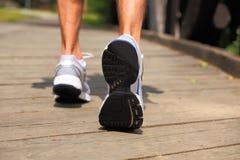Köra i parken - närbild på sportskor och ben Arkivfoto