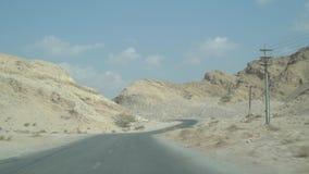 Köra längs den Jebel Jais bergvägen förbigå sidbrant vaggar klippor, runt om skarp krökning, med det avlägsna berget & blått stock video