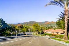 Köra in mot Walker Canyon, sjö Elsinore, under superbloomen; kullar som täckas i Kalifornien vallmo som är synliga i bakgrunden royaltyfri fotografi