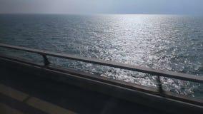 Köra på vägen nära det blåa havet som reser på kustlinjen, stillhetvattenyttersida stock video
