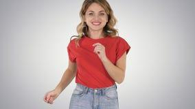 Körande flicka som bär den röda t-skjortan och jeans som ler på lutningbakgrund royaltyfri bild