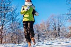 Körande idrottsman nenkvinna som sprintar i yttersida för vinterskogutbildning i kallt snöig väder fotografering för bildbyråer