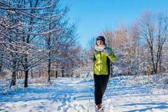 Körande idrottsman nenkvinna som sprintar i yttersida för vinterskogutbildning i kallt snöig väder arkivfoton