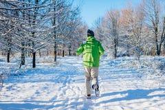 Körande idrottsman nenman som sprintar i yttersida för vinterskogutbildning i kallt snöig väder Aktiv sund livsföring royaltyfri bild
