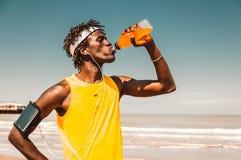 Körande man på stranden som dricker energidrinken royaltyfria bilder