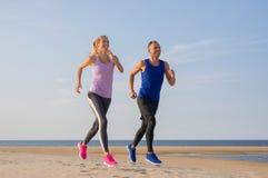 Körande utbildning för löparekonditionpar på stranden arkivbilder