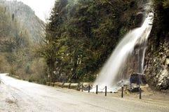 Väg med vattenfallet i nationalparken Rica, Abkhazia Arkivbild