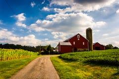 Körbana och röd ladugård i lantliga York County, Pennsylvania fotografering för bildbyråer