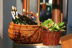 Körbe mit Flaschen Wein und Salaten Lizenzfreie Stockbilder