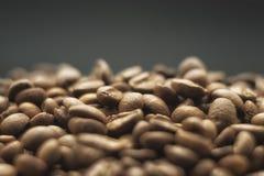 Körner des Kaffees auf einem dunklen Hintergrund Lizenzfreie Stockfotos