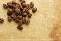 Körner des Kaffees auf Hintergrund des alten Buches. Lizenzfreies Stockfoto
