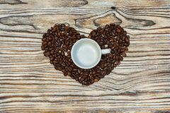 Körner des Kaffees in Form eines Herzens mit einer Kaffeetasse auf einem w Stockbild