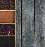 Körner des Kaffees, des Kakaopulvers, des karkade und des schwarzen Tees in einem Kasten, Panorama Stockfotografie