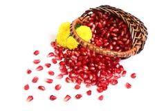 Körner eines Granatapfels, Blumen in einem Korb. Lizenzfreie Stockfotos