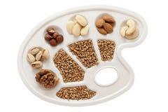 Körner, Nüsse und Mandeln auf Weiß Lizenzfreies Stockfoto