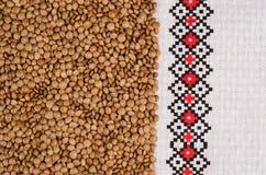 Körner von Linsen auf einem weißen Stoff mit ethnischen Mustern Lizenzfreie Stockfotografie