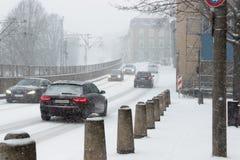 Körning av bilar på entäckt gata i ett snöfall i Tyskland royaltyfri foto