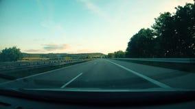 Körning av bilen på den tyska huvudvägen 7 på solnedgångtid arkivfilmer