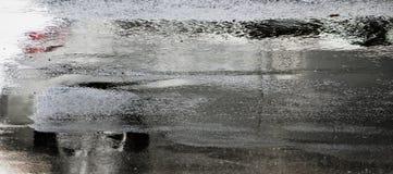 Körning av bilreflexion i den våta stadsgatan i rörelsesuddighet Arkivbilder