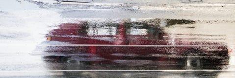 Körning av bilreflexion i den våta stadsgatan i rörelsesuddighet Royaltyfri Bild