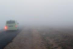 Körning av en bil i ett dimmigt väder royaltyfri bild