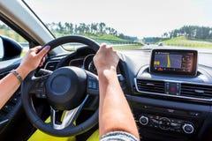 Körning av en bil med navigering Arkivfoto