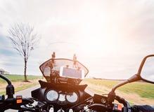 Körning av en motorcykel på våren på asfaltvägen Arkivfoto