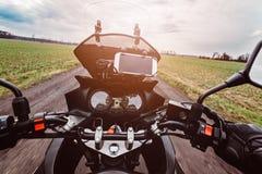 Körning av en motorcykel på våren på grusvägen Arkivfoto