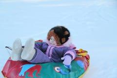 Körning av flickan från en snökulle royaltyfri foto