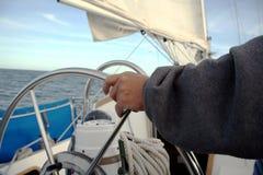 körning av hans segelbåtsjöman Arkivfoton