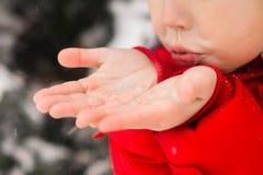 körning av rolig pulkavinter Ett barn blåser snö från gömma i handflatan arkivfoton
