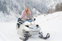 körning av snowmobilekvinnan Arkivfoto