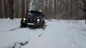 Körning av SUV 6x6 förbi av-vägen i vinterskogen, främre sikt Av-väg stock video