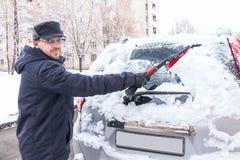 körning av vinter Mannen gör ren bilens fönster från snö Arkivfoton