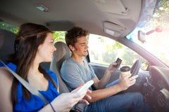 Körning: Chaufför Texting och innehavkaffe royaltyfria foton