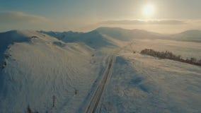 Körning för flera bilar på den iskalla vägen på skymningen nära bergen arkivfilmer