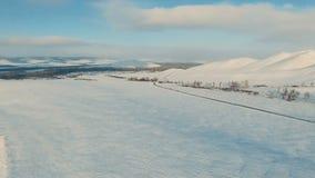Körning för flera bilar på den iskalla vägen på skymningen nära bergen lager videofilmer