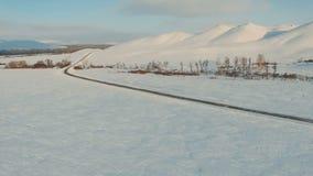 Körning för flera bilar på den iskalla vägen på skymningen till bergen stock video