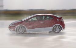 Körning för snabb bil till och med vattnet på vägen Arkivbild