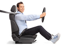 Körning för ung man som placeras på bilsätet royaltyfria bilder