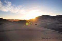 Körning i öknen och solnedgången Arkivfoto