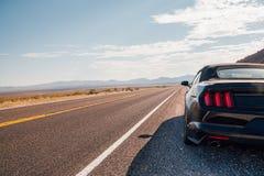 Körning i en svarta Ford Mustang GT Royaltyfria Foton