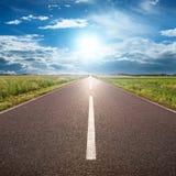 Körning på asfaltvägen in mot solen Fotografering för Bildbyråer