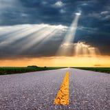 Körning på asfaltvägen in mot solstrålarna Royaltyfria Bilder