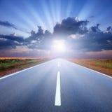 Körning på asfaltvägen in mot solstrålarna Arkivfoto