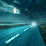 Körning på asfaltvägen på natten in mot billyktorna Fotografering för Bildbyråer
