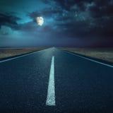 Körning på asfaltvägen på natten in mot månen Royaltyfri Fotografi