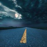 Körning på asfaltvägen på natten in mot månen Arkivbilder